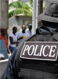 Jamaica: A police officer with his back to the camera faces a crowd.