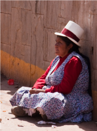 An indigenous woman sits against a wall on a street in Urubamba, Peru.